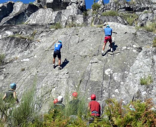 Grupo de pessoas a escalar uma rocha em zona natural com monitores a vigiar