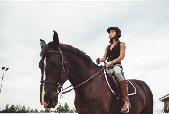 Senhora vestida com equipamento de equitação a passear a cavalo