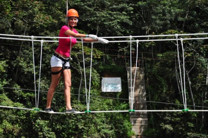 Senhora com equipamento de proteção a passar uma ponte de cordas