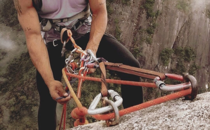 Grande plano de uma pessoa a fazer escalada e a manobrar as cordas numa rocha